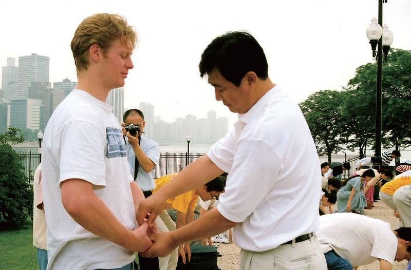 1999年6月,在美国芝加哥法轮大法修炼心得交流会期间,李洪志大师给参加晨炼的学员纠正动作。(明慧网)