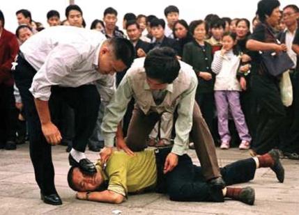 圖為中共便衣警察在眾目睽睽之下,對到天安門廣場和平請願的法輪功學員施暴。(法新社圖片)