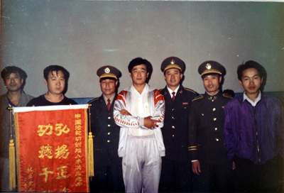 法輪功創始人李洪志先生(中)在北京傳法。因對祛病健身具奇效,且能提高社會的道德水平,1999年7月20日前法輪功在大陸獲得很多政府與民間組織的褒獎。(明慧網)